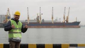 De zeehavenarbeider met een baard en een helm maakt als