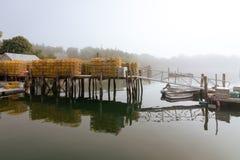 De zeekreeftvallen zitten op een dok in de haven op een mistige ochtend royalty-vrije stock foto
