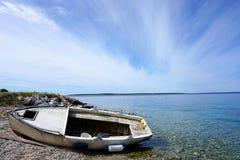 De zeekust met kiezelsteenstrand en oud, schade, roest, vissersboot daalde op het strand royalty-vrije stock afbeeldingen