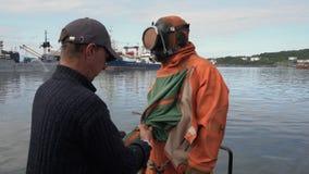 De zeeman helpt om op droog duikkostuum aan scuba-duiker vóór het duiken in oceaan te zetten stock videobeelden