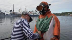 De zeeman helpt om op droog duikkostuum aan scuba-duiker vóór het duiken in overzees te zetten stock videobeelden