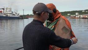 De zeeman knoopt, helpt om droog duikkostuum los aan scuba-duiker uit te trekken na het duiken stock footage