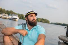 De zeeman zit op de pijler en onderzoekt de afstand royalty-vrije stock foto
