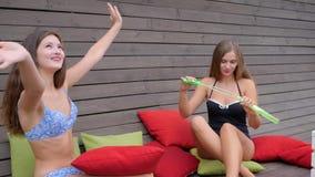 De zeep-partij van meisjes op kussens, lachende vrienden in badpakken maakt bellen op achtergrond van houten muur, stock footage