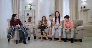 De zeer aantrekkelijke en glimlachende familiemoeder met drie jonge geitjes en oma heeft een prettijd zij samen een videospelletj stock video