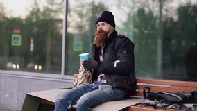 De zeer dronken dakloze mens die aan mensen spreken die dichtbij hem lopen en bedelt voor geld terwijl het zitten op bank bij de  Stock Afbeelding