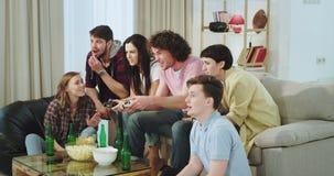 De zeer geïmponeerde en geconcentreerde vrienden hebben samen een prettijd in woonkamer twee van hen die op een videospelletje sp stock video