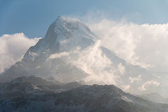 De zeer hoge piek van de sneeuwberg over het wolkenniveau Stock Afbeeldingen