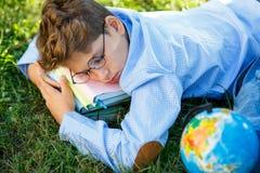 De zeer leuke, jonge jongen in ronde glazen en het blauwe overhemd lezen boek liggend op het gras naast rugzak en bol Onderwijs stock foto