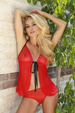 De zeer mooie vrouw bevindt zich in het rode zwempak bij het zwembad Stock Fotografie