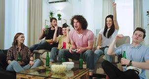 De zeer opgewekte multi etnische vrienden die in woonkamer letten op hoe hun twee vrienden op een videospelletje zijn, wat van he stock videobeelden