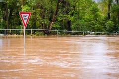 De zeer overstroomde weg en geeft teken uiting Stock Foto