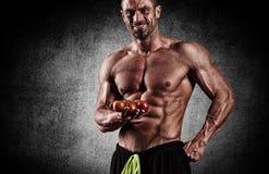 De zeer spier sportieve kerel het drinken proteïne in donkere gewichtsroo Royalty-vrije Stock Afbeelding