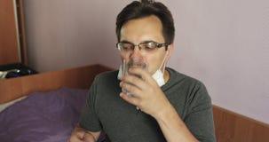 De zeer zieke mens drinkt een geneeskunde tijdens de epidemie stock footage