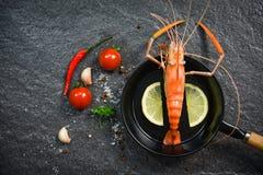 De zeevruchten van garnalengarnalen kookten hete pan met citroenkruiden en kruid op donkere achtergrond stock foto's