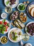 De zeevruchtensnacks dienen - ingeblikte sardines, mosselen, octopus, druif, olijven, tomaat en twee glazen witte wijn op houten  Stock Fotografie