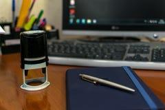 De zegel voor documenten, de blocnote en de pen liggen op een houten bureau royalty-vrije stock afbeelding