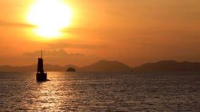 De zeilboot drijft op het overzees, als zonreeksen op de horizon stock videobeelden