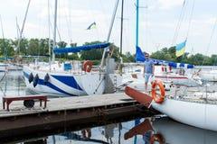 de zeiler gaat van boot op pijler De jonge mens legde zijn jacht in rivierdok vast Mannelijke hobbys en levensstijl royalty-vrije stock foto