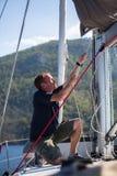 De zeiler trekt de kabel op de mast, op zijn varende yaht boot Stock Foto