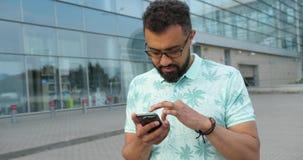De zekere aantrekkelijke Afrikaanse mens in oogglazen doorbladert en texting op de mobiele telefoon dichtbij de glasbouw rotating stock videobeelden