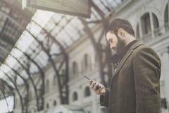De zekere aantrekkelijke zakenman kleedde zich in modieuze kleren die bericht texting zijn mobiele telefoon bij de zaal van spoor stock afbeeldingen