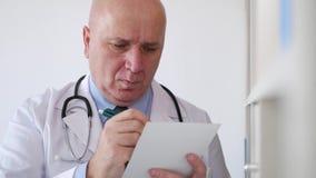 De zekere arts in een het ziekenhuisruimte schrijft een medisch recept voor een geduldige behandeling stock video