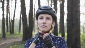 De zekere jonge fietservrouw zet op helm kijkend aan de camera Triatlonconcept stock footage