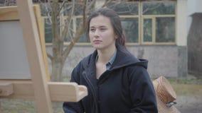 De zekere jonge zitting van de meisjesschilder voor houten schildersezel die rond eruit zien Vrouwelijke kunstenaar in toevallige stock video