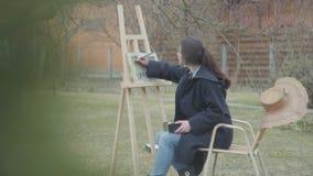 De zekere jonge zitting van de meisjesschilder voor houten schildersezel die rond eruit zien Vrouwelijke kunstenaar in toevallige stock footage