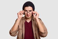 De zekere knappe gebaarde krullende mens houdt handen op rand van bril, kijkt aandachtig, gekleed in zwarte hoed en beige overhem stock foto