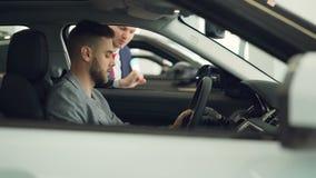De zekere koper van de mensenauto zit in bestuurders` s zetel in nieuwe auto binnen moderne toonzaal en spreekt aan verkoper stock video