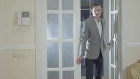 De zekere makelaar in onroerend goed openingsdeur die nieuw luxehuis ingaan, toont een jong succesvol echtpaar een nieuw huis stock footage