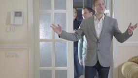 De zekere makelaar in onroerend goed openingsdeur die nieuw luxehuis ingaan, toont een jong succesvol echtpaar een nieuw huis stock video