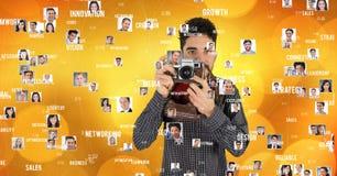 De zekere mannelijke die camera van de fotograafholding met het vliegen portretten wordt omringd royalty-vrije stock afbeeldingen