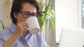 De zekere rijpe onderneemster werkt met laptop, drinkend koffie in huisbureau stock video