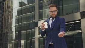 De zekere zakenman drinkt drank, bekijkend horloge, die zich dichtbij de bureaubouw bevinden stock videobeelden