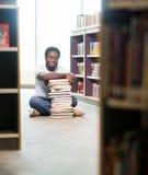 De zekere Zitting van Studentenwith stacked books binnen Stock Foto's