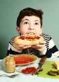 De zelf gemaakte reusachtige hotdog van de jongensbeet Royalty-vrije Stock Fotografie