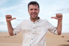 De zelf-tevreden en trotse Kaukasische jonge mens kijkt vooruit tonend met wijsvingers op zich Royalty-vrije Stock Foto's