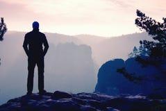 De zelf zekere wandelaar in akkimbo stelt op de piek van rots stock fotografie
