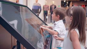 De zelfbediening, kindvrienden gebruikt elektronische gids voor onderzoeksinformatie over plaats van winkel bij winkelcentrum stock footage