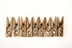 De zelfde oude houten wasknijpers liggen op een rij stock fotografie