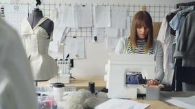 De zelfstandige kledingsontwerper werkt met naaimachine, stikken textiel en het bekijken schetsen die liggen stock footage