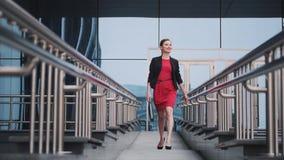 De zelfverzekerde bedrijfsvrouw in een rode kleding loopt tegen de achtergrond van moderne gebouwen Portret van een jonge vrouw stock videobeelden