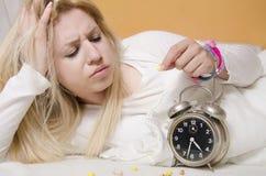 De zenuwachtige jonge vrouw schuint slaap af, die slaappil nemen stock afbeelding
