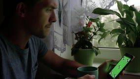 De zenuwachtige mens drinkt thee en gebruikt zijn telefoon stock videobeelden