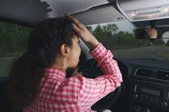 De zenuwachtige vrouwelijke bestuurder zit bij wiel, heeft ongerust gemaakt uitdrukking zich als afraids om auto voor eerste keer stock afbeeldingen