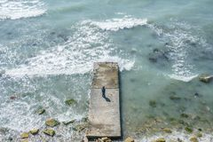 De zes-jaar-oude jongen bevindt zich op een pijler op zee tijdens een onweer met golven Op zee de lente zonnige dag Stock Afbeelding