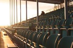 De zetels van de tribune met twee mensen in heldere zon Stock Fotografie